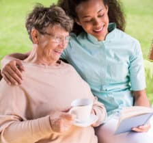 happy caregiver and senior woman while reading